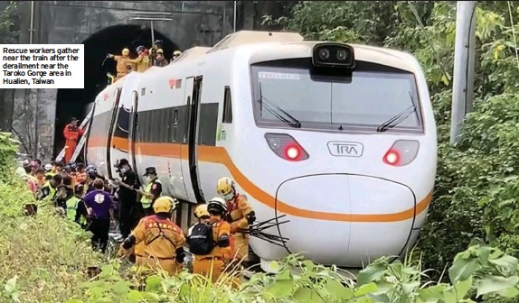 ??  ?? Rescue workers gather near the train after the derailment near the Taroko Gorge area in Hualien, Taiwan