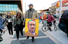 ?? Reuters ?? A man carries a portrait of George Floyd as people gather outside the Barclays Center in Brooklyn on Tuesday.