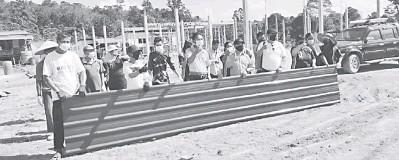 ??  ?? BANTUAN: Paulus (lima kanan) menyerahkan bantuan atap kepada penduduk Kampung Meresam Penganan semalam.