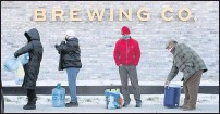 ?? AUSTIN AMERICAN-STATESMAN VIA THE ASSOCIATED PRESS ?? People waited in line to fill up containers with water at Meanwhile Brewing Company in Austin, Texas, on Feb. 19 during a citywide boil water notice caused by the winter storm.