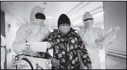 """?? MTV DOCUMENTARY FILMS ?? An elderly woman with COVID-19 is escorted by two nurses after being admitted to a hospital in Wuhan, China, in a scene fromthe documentary """"76 Days."""""""
