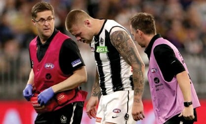 ?? Photograph: Richard Wainwright/AAP ?? Collingwood's Jordan de Goey leaves the field with a bleeding nose during the round five AFL match against West Coast.