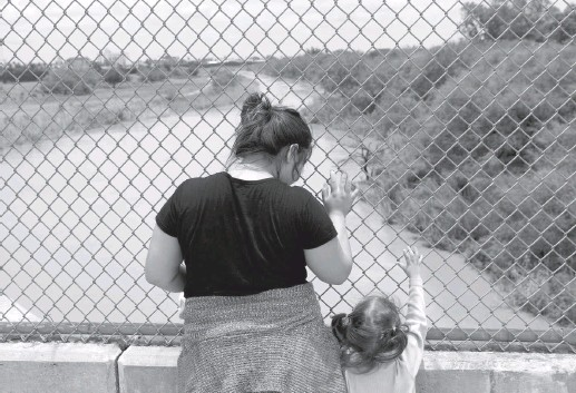 ?? LOREN ELLIOTT/REUTERS ?? A Honduran mother seeking asylum with her 3-year-old daughter waits on the Mexican side of the international bridge to Brownsville, Tex., after being denied entry by U.S. officers last weekend.