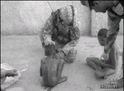?? CBS NEWS VIA ASSOCIATED PRESS ?? In this video image, soldiers tend to children at the orphanage in northern Baghdad. Photos showed some boys tied to beds, others lying on hard floors in their own waste.