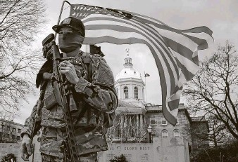 ?? Winslow Townson / Associated Press ?? An armed protester stands in front of the statehouse on Sunday in Concord, N.H. Some statehouses were surrounded by new protective fences and had boarded-up windows.