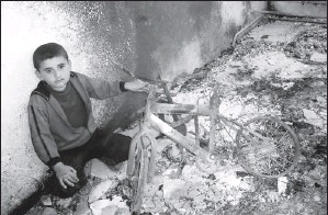 ?? Higher Committee for the Syrian Revolution via Afp/getty Images ?? Regime faces deadline today: A boy holds a burnt bike in a destroyed home in the Syrian province of Daraa. President Bashar Assad's crackdown on a year-old uprising has left 9,000 people dead.