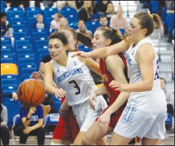 ?? Herald photo by Dale Woodard ?? University of Lethbridge Pronghorns Katie Keith (left) and Amy Mazutinec reach for a rebound against Calgary Dino Bobbi-Jo Colburn in second half Canada West play Saturday night at the 1st Choice Savings Centre.