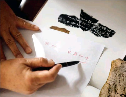??  ?? At present, identification of oracle bone inscriptions has become a discipline involving diverse subjects such as archeology, history and philology. Pictured is Huang Tianshu explaining how to identify a specific character on an oracle bone. by Ma Yue