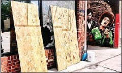 ?? AFP ?? Boards lean against a building where multiple gunshots were fired near George Floyd memorial square in the US city of Minneapolis, Minnesota state.