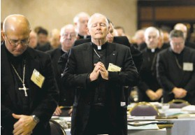 ?? J. Scott Applewhite / Associated Press 2003 ?? Cardinal Theodore McCarrick (center) –oins his fellow clergy in prayer at the 2003 5.S. Conference of Catholic Bishops meeting in Washington, .C.