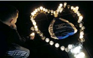 ?? VALERY HACHEVALERY HACHE/AFP/Getty Images ?? A boy lays a candle during a candlelight vigil for Olympic goldmedallist Camille Muffat Tuesday in Nice, France. Muffat was one of 10 people killed Monday during a crash in Argentina.