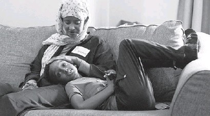 ?? KAREN DUCEY/AP ?? Shukri Olow, left, a Muslim woman who is running for a council seat in Kent, Washington, snuggles with her son. Young adult Muslim Americans grew up amid the aftershocks of the Sept. 11, 2001, terrorist attacks.