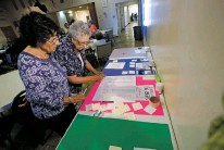 ?? LUIS SÁNCHEZ SATURNO/THE NEW MEXICAN ?? Beatrice Chavez Ortiz, left, and Linda Lury, Santa Fe High School Class of 1960, look at a list of people from their high school days who have died. A reunion of graduates from the Santa Fe area was held Friday.