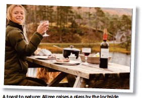 ??  ?? A toast to nature: Alizee raises a glass by the lochside