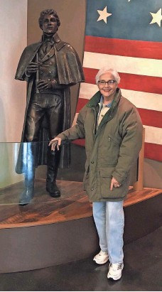 ?? COURTESY OF SHIRLEY CAROLE ISHAM ?? Shirley Carole Isham, with a statue of national anthem author Francis Scott Key, an ancestor, says Colin Kaepernick is wrong.