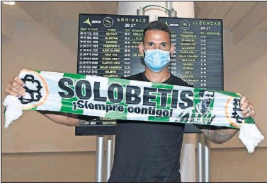 ??  ?? Willian José posa con una bufanda del Betis a su llegada ayer al aeropuerto de Sevilla.