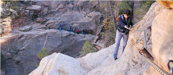 ?? PHOTOS: GREG OLSEN ?? A hiker grabs a chain secured to the wall at Hidden Canyon Trail in Utah's Zion National Park. The sheer sandstone walls and the rock formations are spectacular.