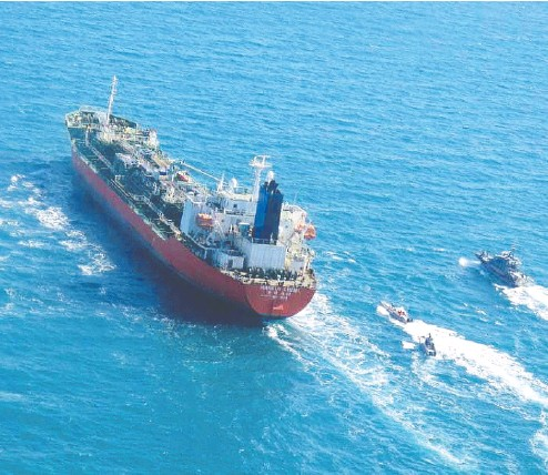 ?? TASNIM NEWS / AFP via Gett y Imag es ?? A South Korean-flagged tanker is escorted by Iran's Revolution­ary Guards navy after being seized in Persian Gulf