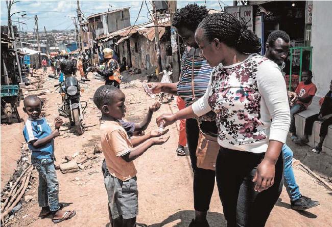 ?? // AFP ?? Un grupo de voluntarias de una ONG ofrecen gel hidroalcohólico a los niños en Kibera, un 'slum' de Nairobi