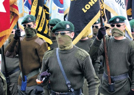 ??  ?? Show of force: Masked members of the UDA — which declared a ceasefire in 1994 — march in the Lower Shankill Road area