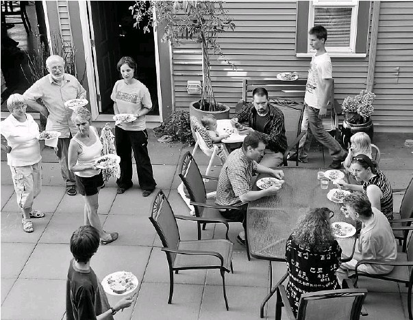 ?? SAM LEUNG / CANWEST NEWS SERVICE ?? Cranberry Commons Cohousing members eat dinner in the community courtyard. Niche communities such as this one in Burnaby, B.C., have been gaining popularity across the country.