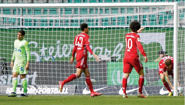 ?? Associated Press ?? ↑ Bayern Munich's Jamal Musiala (centre) celebrates after scoring a goal against VFL Wolfsburg during their German League match on Saturday.