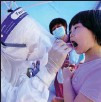 ?? JI CHUNPENG / XINHUA ?? A girl is tested for COVID-19 by a medical worker on Wednesday at a residential compound in Jiangning district, Nanjing, Jiangsu province.