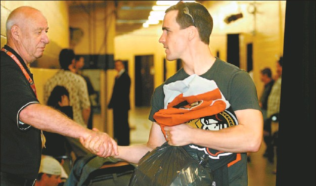 ?? JULIE OLIVER, THE OTTAWA CITIZEN ?? Carrying some of his personal belongings along with a team jersey, Senators defenceman Wade Redden shakes the hand of longtime security guard Bill Brooks before leaving Scotiabank Place.
