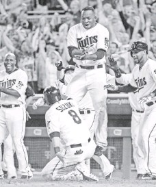 ?? JESSE JOHNSON, USA TODAY SPORTS ?? Miguel Sano, leaping as Kurt Suzuki scores the winning run in a game in August, is among Latin Americans helping the Twins.