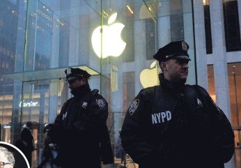 ?? JEWEL SAMAD, AFP/GETTY IMAGES ?? Police stand guard during a demonstration outside the Apple store on Fifth Avenue in New York. Apple says it will not build a back door to the iPhone.
