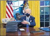 ?? EVAN VUCCI/AP ?? Pres­i­dent Joe Bi­den signs a se­ries of ex­ec­u­tive or­ders on In­au­gu­ra­tion Day at the White House in Wash­ing­ton.