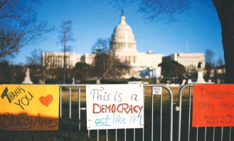 ?? ASTRID RIECKEN FOR THE WASHINGTON POST ?? Pro-democracy signs line a fence near the U.S. Capitol on Saturday, three days after a mob that was incited by President Trump stormed and vandalized the building.
