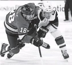 ?? AP ?? The Jets' Bryan Little (18) and the Coyotes' Christian Fischer fight for position on Saturday in Winnipeg, Manitoba.
