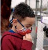 ?? ASSOCIATED PRESS ?? A boy gets his temperatur­e checked at an elementary school in Maywood, California. Some of the state's schools have slowly begun to reopen this week for in-person instructio­n.
