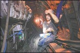 ??  ?? A coal miner breaks his fast underground.