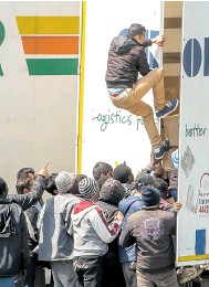 ??  ?? UK BOUND: Migrants boarding a lorry in Calais