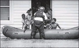 ?? ANDREW DYE/WINSTON-SALEM JOURNAL ?? A firefighte­r helped residents into a raft at Creekwood Apartments as firefighte­rs evacuated the complex because of flooding on Thursday in Winston-Salem, N.C.