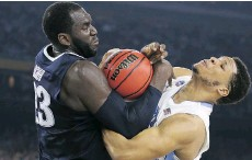 ?? STREETER LECKA/GETTY IMAGES ?? Daniel Ochefu of the Villanova Wildcats and Kennedy Meeks of the North Carolina Tar Heels fight for the ball in the NCAA men's final at NRG Stadium on Monday night in Houston.