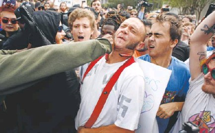 ?? Brian Blanco, Getty Images ?? A man wearing a swastika-covered shirt gets punched by an unidentified member of the crowd near the site of a speech by white nationalist Richard Spencer at the University of Florida in Gainesville, Fla., on Thursday.