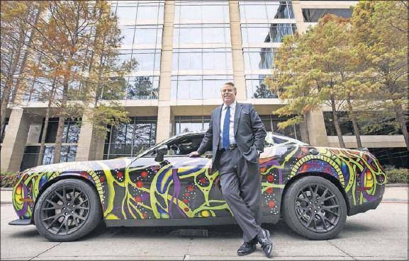 ?? Ashley Landis/Staff Photographer ?? Clifford Fischer, a tenant rep who's considered a force to be reckoned with, poses with his custom-wrapped 2015 Dodge Challenger Hellcat outside Fischer & Co. headquarters in Dallas. His longtime clients include FedEx, AT&T, IBM, Mary Kay and Dow Jones.