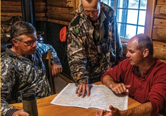 ??  ?? Hunters at Chandler Lake Camps and Lodge consider their plan of attack before hitting the North Woods.