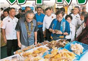 ??  ?? 連達立夫、范長錫陪同首長參觀各零食小吃攤位。