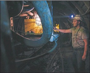 ??  ?? A Bosnian coal miner works in an underground tunnel.