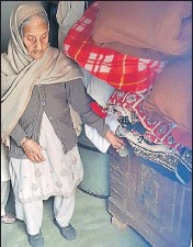 ?? HT PHOTO ?? Gur­dayal Kaur stands next to the wooden box in which she has kept the body of her grand­son at Hathur vil­lage near Ja­graon on Tues­day.