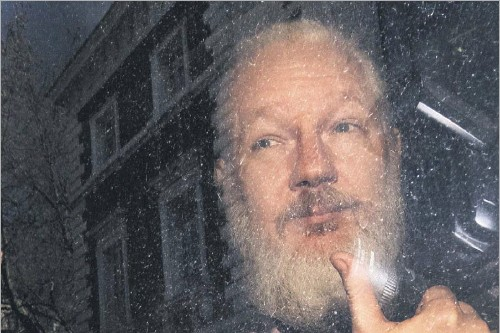 ?? Victoria Jones/the Associated Press ?? Sporting a full beard and slickedback gray hair, Wikileaks founder Julian Assange gestured Thursday through the window of a police van as he was removed from the Ecuadorian Embassy in London.