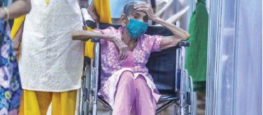 ?? Associated Press ?? ↑ An elderly woman waits to receive vaccine at a vaccination centre in Mumbai on Sunday.