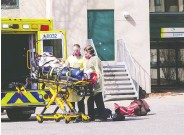 ?? JOHN MAHONEY /POSTMEDIA NEWS ?? Paramedics wheel a resident out of Résidence Herron in Dorval, Que., on Wednesday.