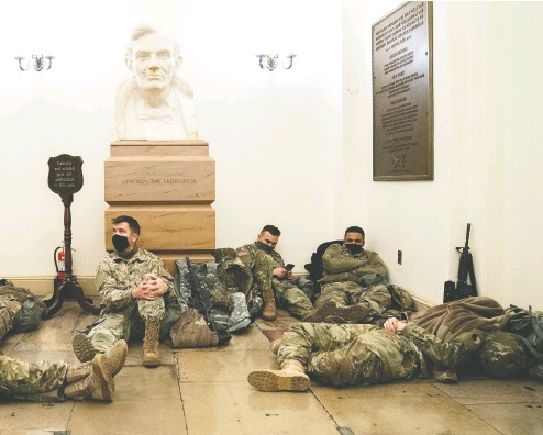 ?? STEFANI reynolds / GETTY IMAGES ?? Members of the National Guard with rifles rest in the U.S. Capitol on Wednesday as security has been increased throughout Washington leading up to the presidential inauguration nest week.