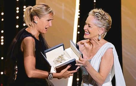 ?? FOTO REUTERS ?? Hlavní cenu v Cannes tentokrát předávala žena ženě. Francouzská režisérka Julie Ducournauová ji obdržela z rukou herečky Sharon Stoneové.
