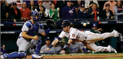 ?? Associated Press ?? Josh Reddick dives past catcher Austin Barnes to score from first on an infield hit and a throwing error, giving Houston a 5-1 lead.